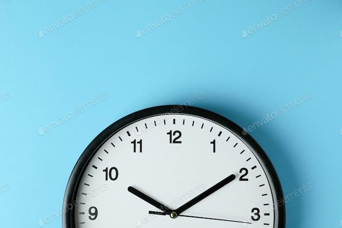Standard black office clock on blue background