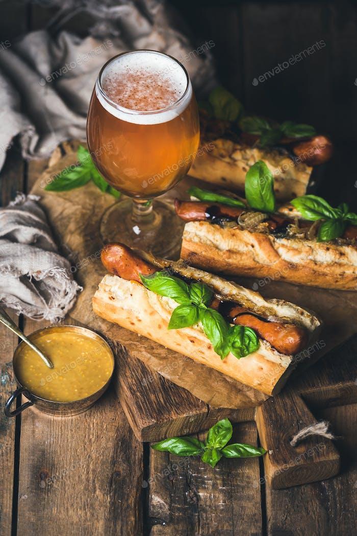 Glas Weizenbier und gegrillte Wursthunde im Baguette