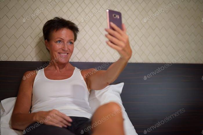 Happy mature beautiful tourist woman taking selfie in the bedroom