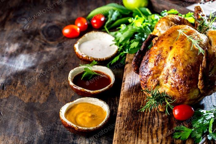 Gebratenes Huhn mit Rosmarin und Saucen auf Holzbrett