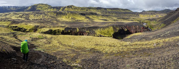 Woman traveler with backpak walking on the Laugavegur trail in Iceland, Europe