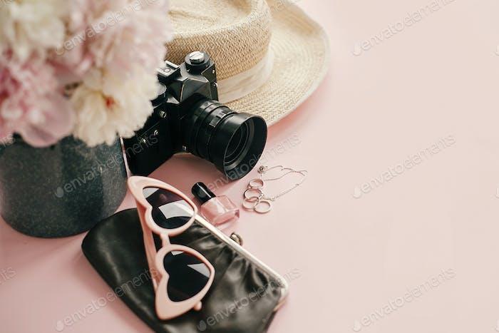 Stylish girly image of pink peonies, photo camera, retro sunglasses