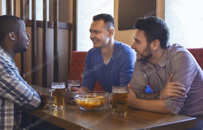 Cheerful mates talking at bar while drinking beer