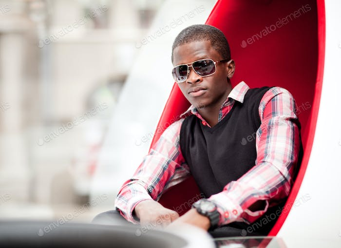Young handsome african man in stylish casual clothing and sunglasses sitting in big red egg shaped