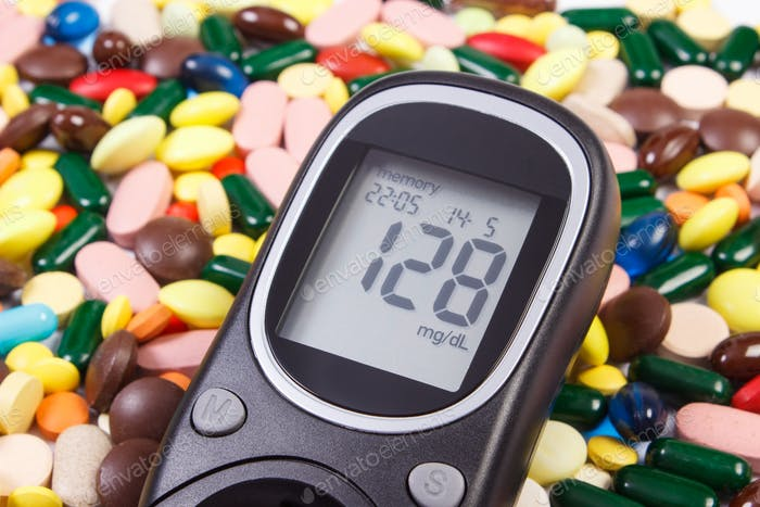 Glucometer with sugar level and heap of medical pills or capsules
