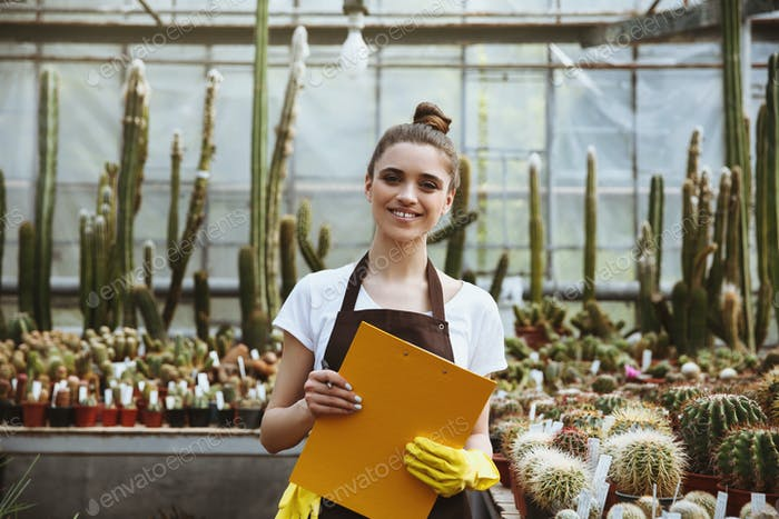 Happy young lady standing in greenhouse holding clipboard