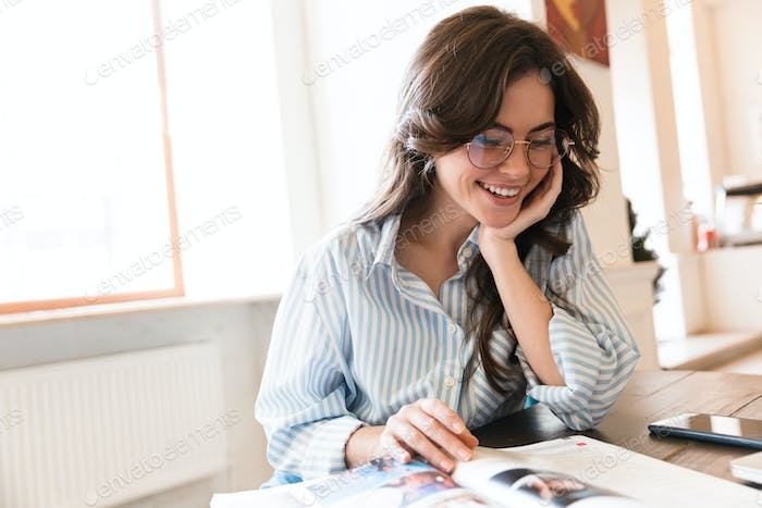 Attractive young brunette woman studying in the cafe indoors