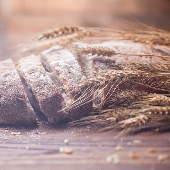 Bread and wheat on wooden table, shallow DOF