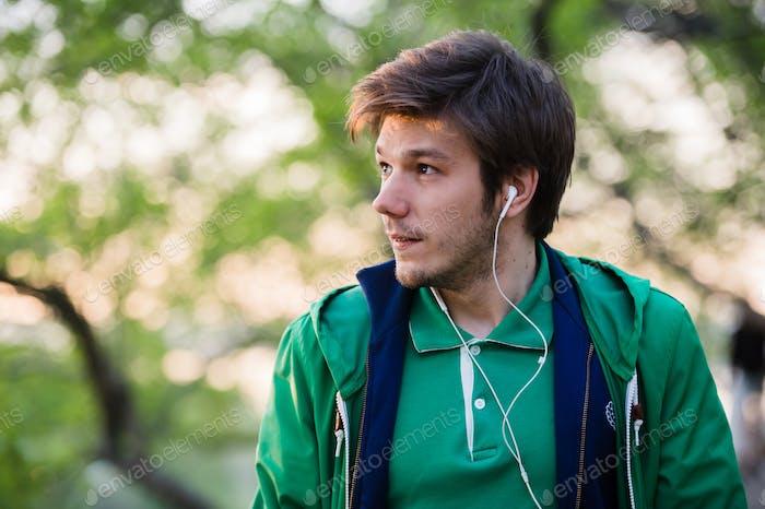 Junger Mann mit Ohrhörern Musik hören. Porträt der Person im Park, der denkt an