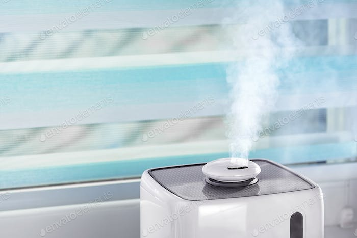 The white ultrasonic humidifier on a window moistens dry air