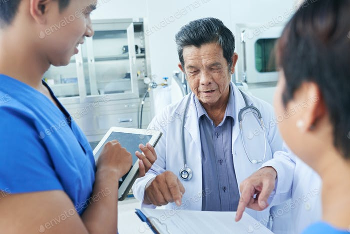 Doctors checking medical history of patient
