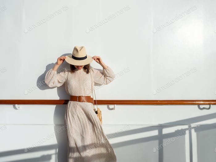 Young woman in a hat by the wall