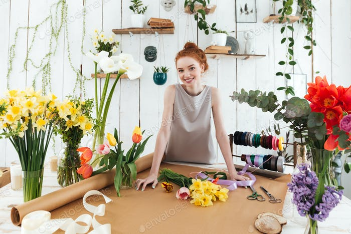 Young pretty florist standing near table with flowers and looking camera