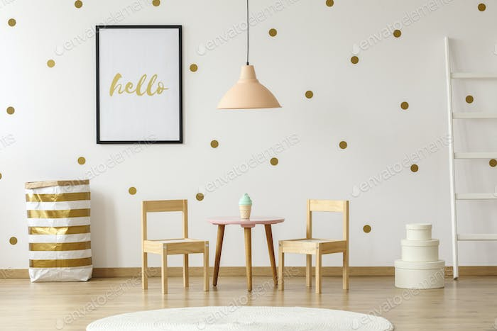 Pastel lamp above table and wooden chairs in white and gold kid'