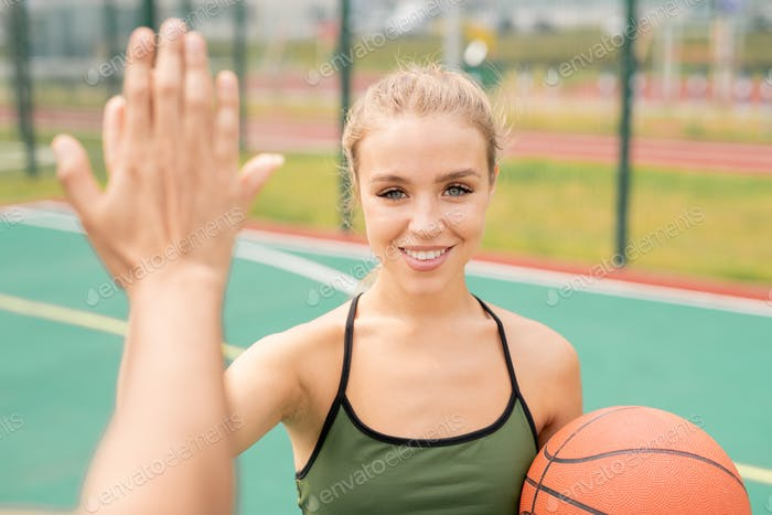 Pretty young blonde woman in activewear giving high-five to her friend
