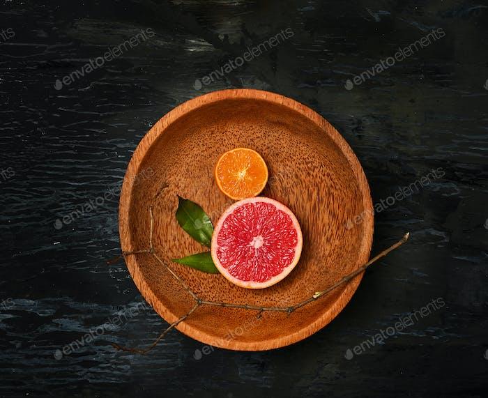 Grapefruit citrus fruit halves on wooden plate