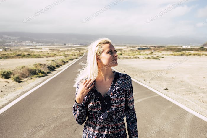 beautiful lonely blonde caucasian young girl walk  in a long road
