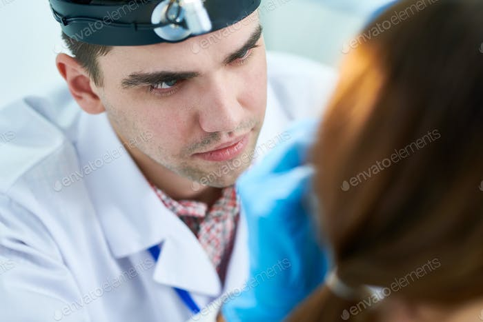 Young Otolaryngologist  Examining Patient