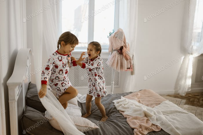 Two little girls in their pajamas are having fun jumping on a bed in a sunlit cozy bedroom