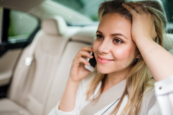 Business woman with smartphone sitting on back seats in taxi car.