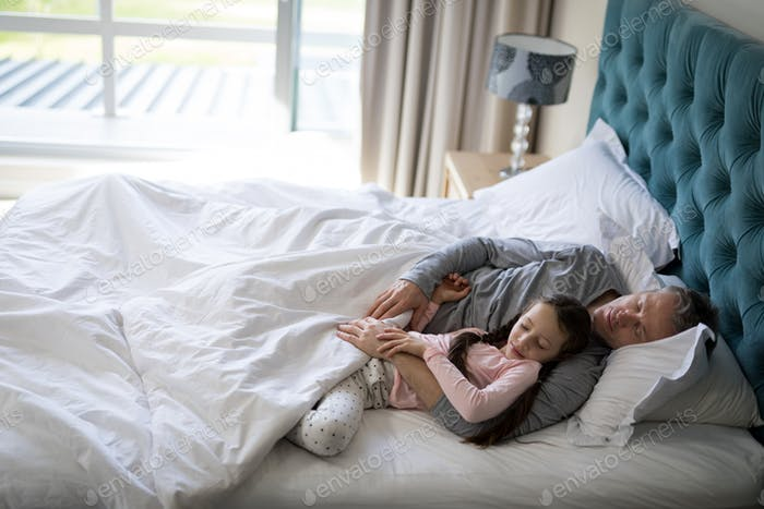 Father and daughter sleeping together on bed in bedroom