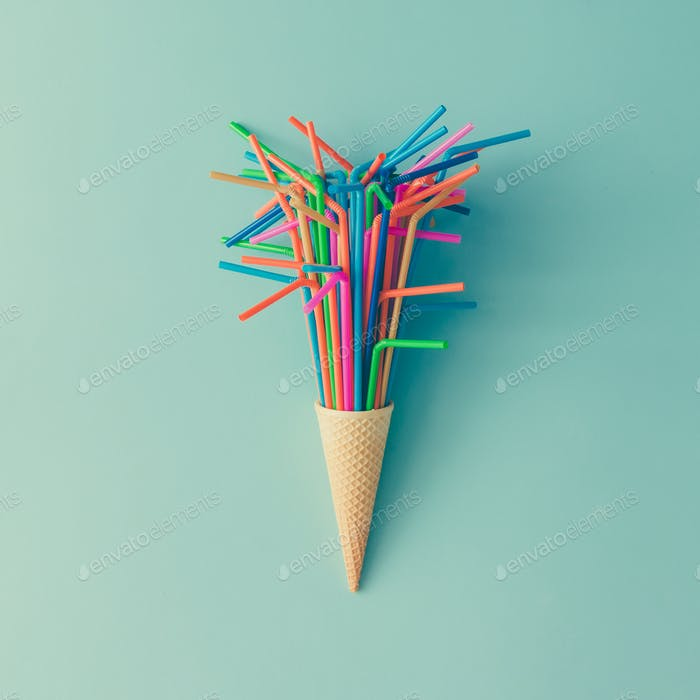 Ice cream cone with colorful drinking straws on bright blue background.