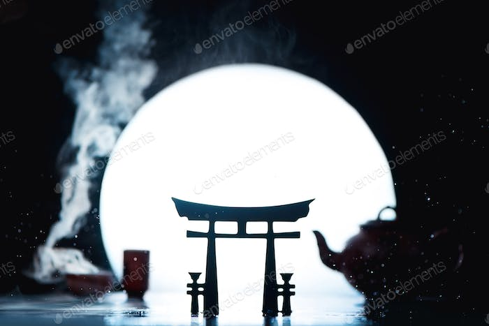 Torii gates silhouette with full Moon and tea cups and teapot. Creative hot drink photography with