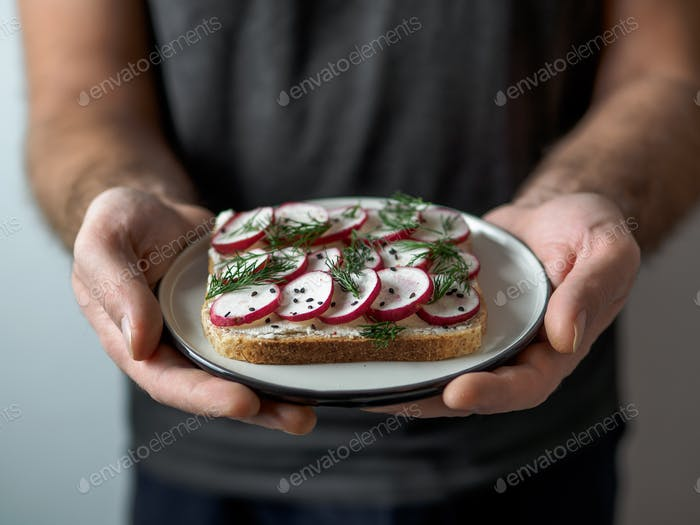 Vegan sandwich with radish in male hands