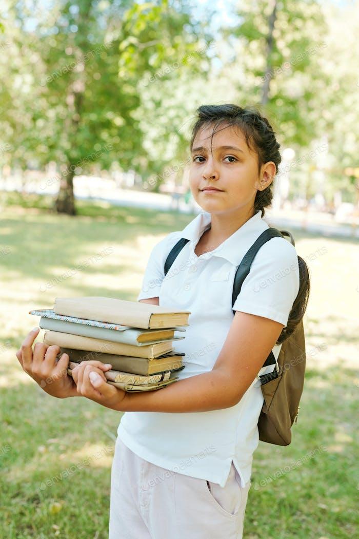 Indische Schülerin mit Stapel von Büchern