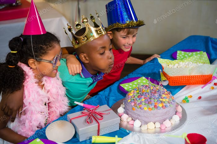 Boy blowing candles on cake