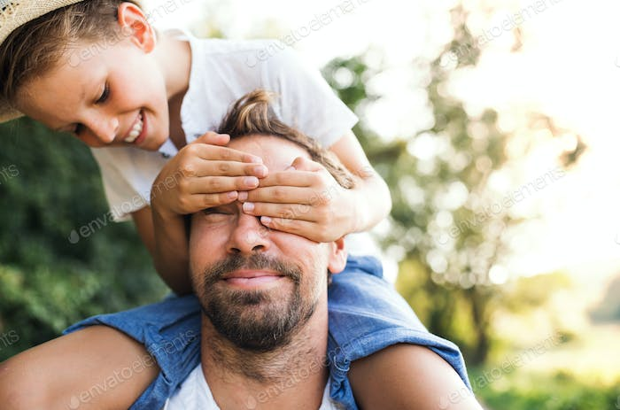 Young father in nature giving small son a piggyback ride, boy covering man's eyes.