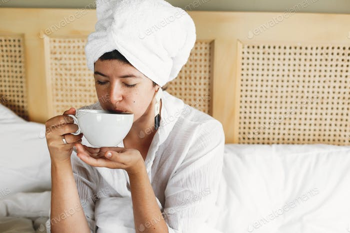 Beautiful happy young woman drinking coffee in bed