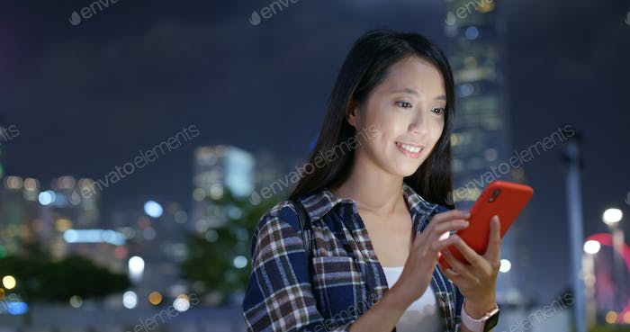 Woman use mobile phone online in the city at night