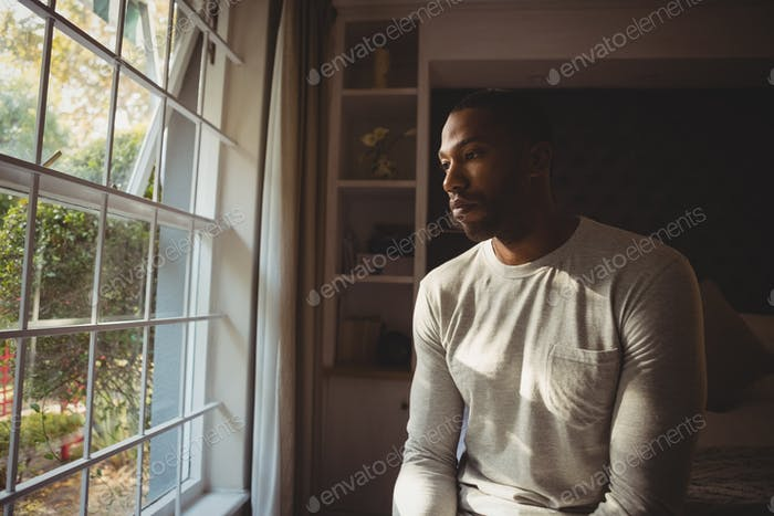 Thoughtful man sitting by window at home