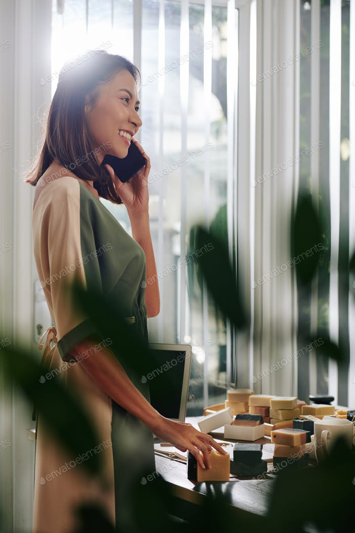 Businesswoman talking on phone with customer