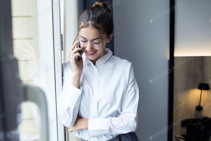 mujer de negocios bastante joven hablando con su teléfono inteligente de pie