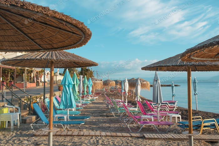 Ionian sea beach with colorful chaise lounges and staw umbrellas.