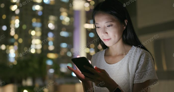 Young woman working on cellphone in city at night
