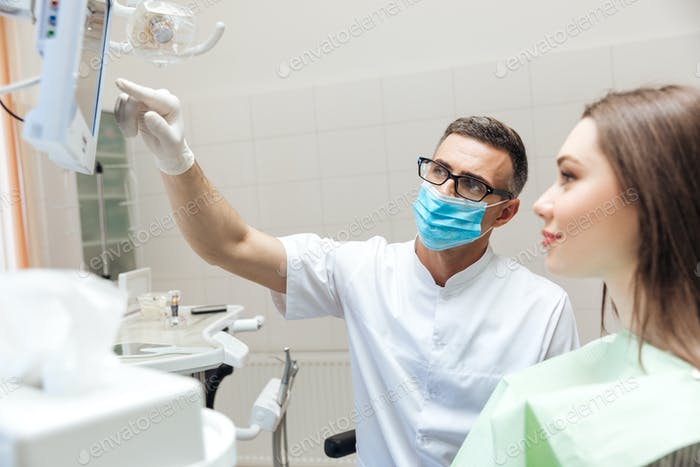 Dentist explaining x ray picture to patient on LED monitor