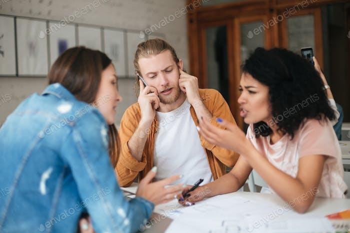Junger Mann im Gespräch auf seinem Handy, während zwei hübsche Mädchen emotional etwas diskutieren