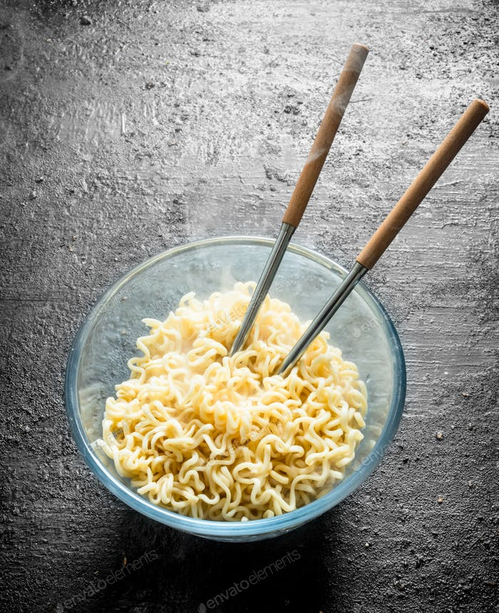 Hot instant noodles in bowl with chopsticks.