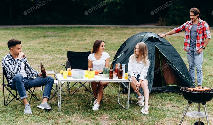 Young guys in the camping next a tent have a lunch and have a funny time