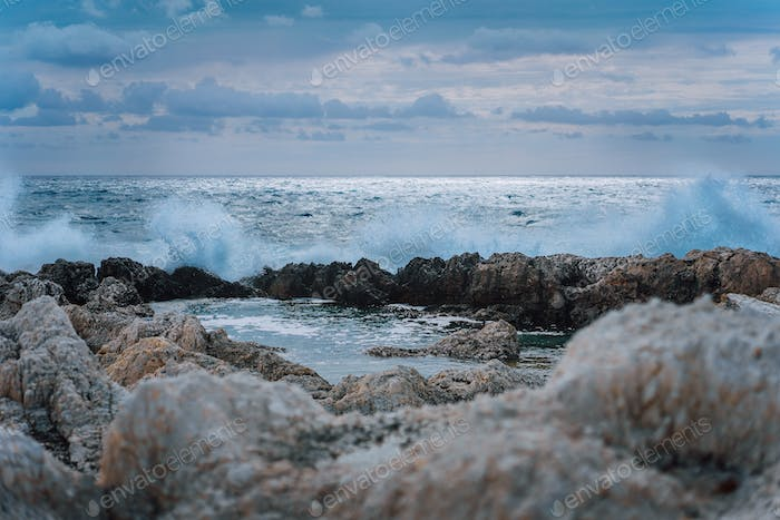 Waves splashing against rocky coastline and building natural pools. Dramatic cloudscape