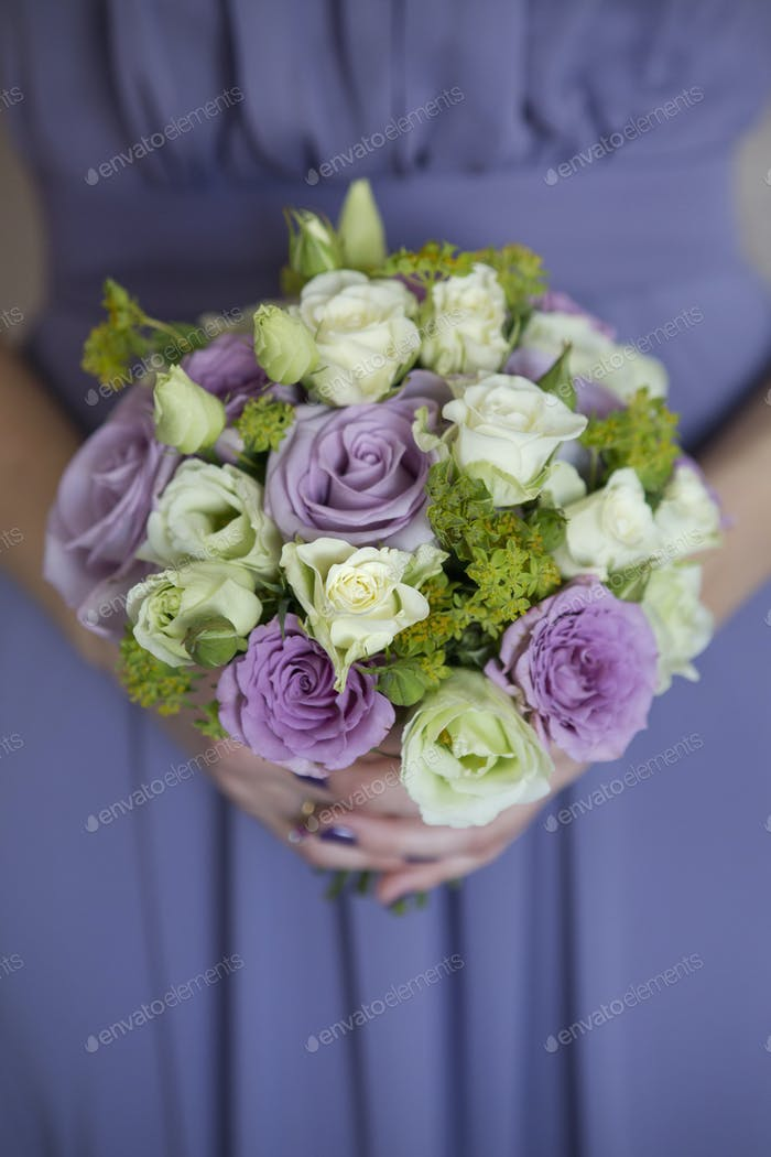 A woman in a blue dress holding a bouquet of roses.