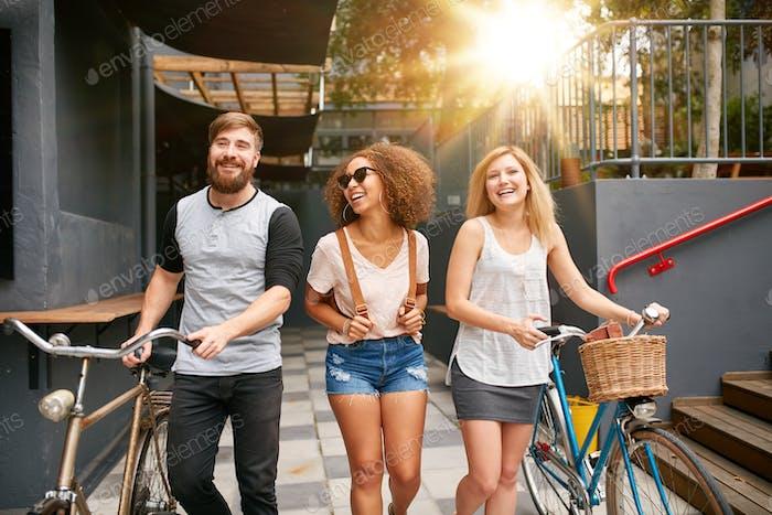 Drei junge Erwachsene zu Fuß zusammen mit dem Fahrrad