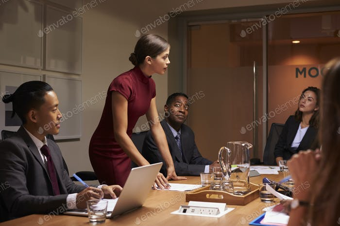 Female manager  standing to address team at business meeting