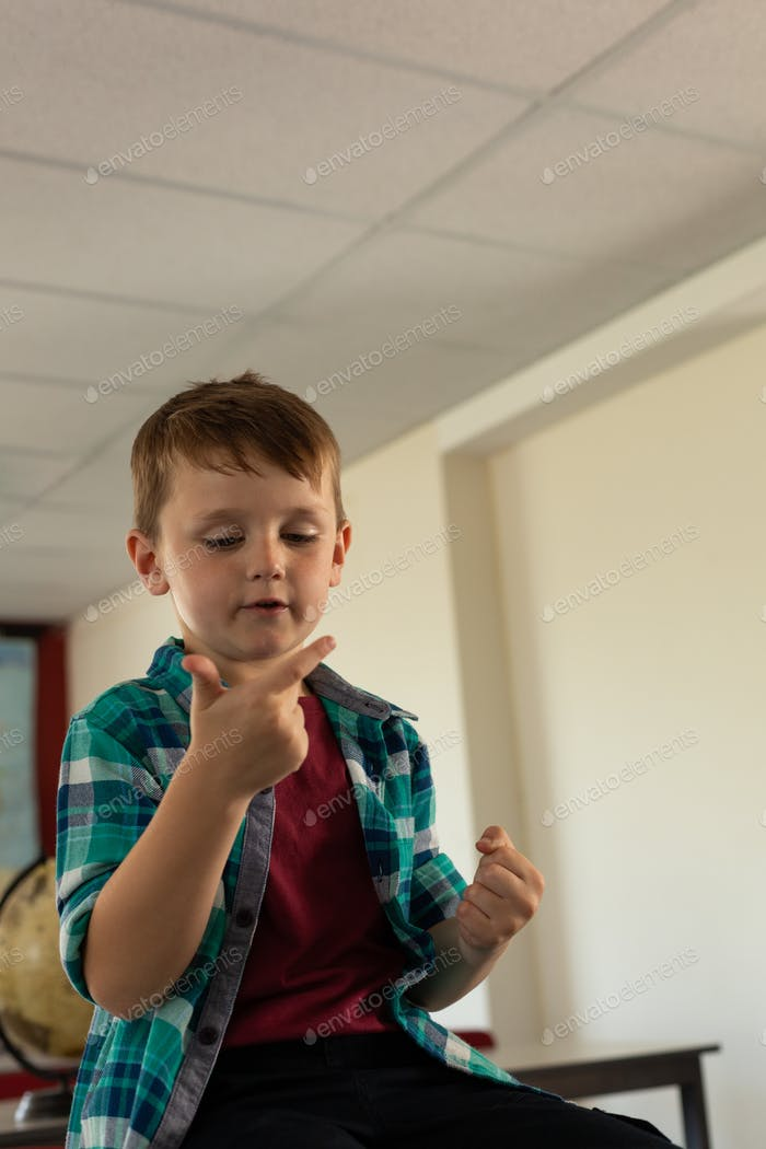 Boy sitting over desk and counting with his finger in classroom at elementary school