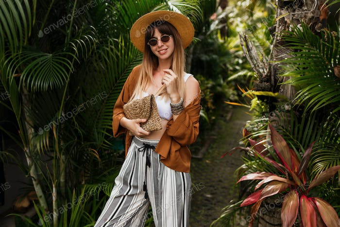 woman in straw hat posing on tropical palm leaves background in Bali