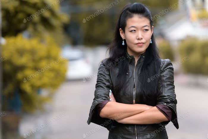 Portrait of beautiful Asian rebellious woman with arms crossed outdoors