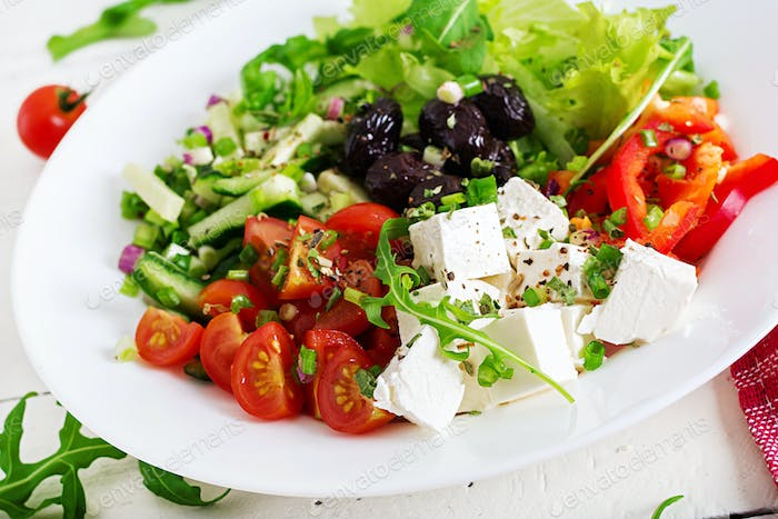 Greek salad of fresh cucumber, tomato, sweet pepper, lettuce, onion, feta cheese and black olives